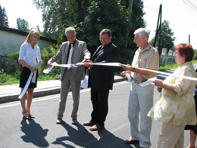 Petr Polášek (uprostřed) a starostové Skorošic a Vidnavy přestřihli slavnostně pásku u nově zrekonstruované silnice.