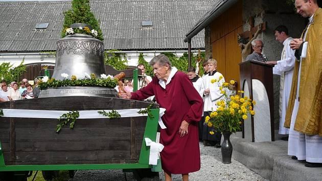 Věra Banková poklepává dřevěným kladívkem na nové zvony. Je to vůbec poprvé, kdy lidé uslyšeli jejich zvuk.