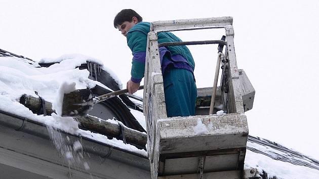 Odstraňování sněhu ze střechy domu v centru Šumperku