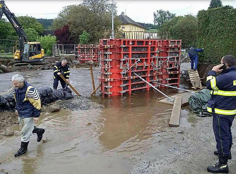 Jednotky profesionálních i dobrovolných hasičů staví protipovodňové zátarasy z pytlů s pískem v Rapotíně okolo Desné na Olomoucku.
