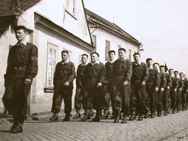 Oddíl tehdejších Lidových milicí z podniku MEZ Mohelnice pochoduje na 1. máje roku 1952.