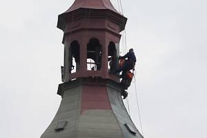 Skupina lezců natírá báň kostela svatého Bartoloměje v Zábřehu.