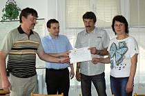 Starosta Rájce Vladimír Hroch a ředitel Charity Zábřeh Jiří Karger (zleva) předávají darovací šek manželům Strašilovým.