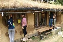 Dobrovolníci v osadě Zastávka při práci na budově zvané Hobitín.