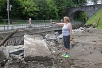 Šarlota Koryťáková ukazuje na místo, kde stával most spojující pozemek u jejího domu se silnicí. Povodeň most strhla.