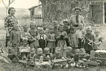 SHRAČKAMI. Děti zmateřské školy vNedvězí vroce 1958 se svými učitelkami a hračkami. Některé znich mají děti i vsoučasnosti, například legendární houpací kohouty.