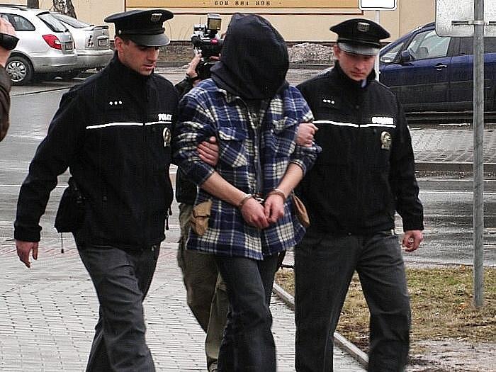 Policisté odvádějí zatčeného mladíka