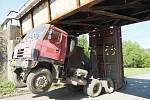 Řidič Tatry s nesklopenou korbou vjel pod most. O konstrukci zaháčil a poškodil ji.