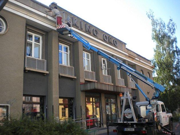 Z kina Oko dělníci sundavají oprýskanou fasádu.