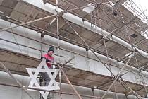 Dělník nese do štítu synagogy šablonu židovské hvězdy, kterou v roce 1939 nechali odstranit nacisté