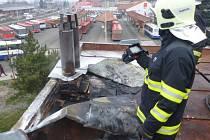 Hasič kontroluje místo požáru na střeše hospůdky u autobusového nádraží termokamerou.