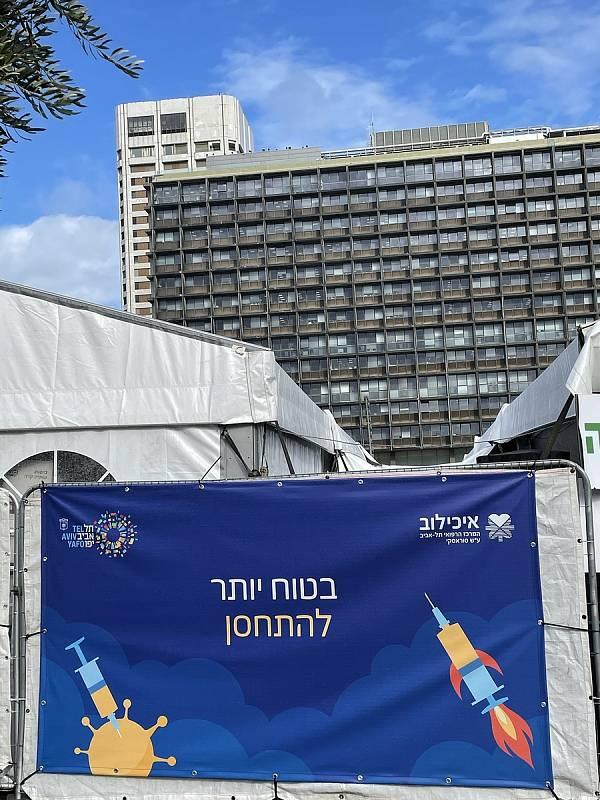 """Očkovací stan v Tel Avivu. NA baneru nápis Bezpečnější je očkovat"""""""