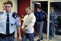 Na snímku jsou obžalovaní Jiří Znojil (v bílé mikině), Josef Král (v modré mikině, za prosklenými dveřmi) a Miroslav Červeňák (v černé mikině s bílým znakem), přiváděni vězeňskou stráží do jednací síně