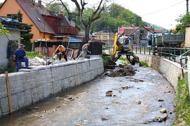 Pracovníci stavební firmy opravují koryto potoka v Javorníku poškozené povodní.