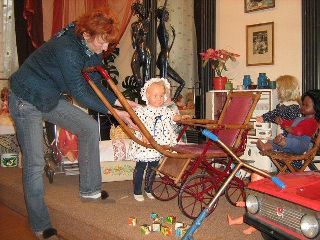 Hana Polášková upravuje zapůjčenou panenku. Výstava ukazuje, s jakými hračkami si hráli naši rodiče a prarodiče. Nejcennější exponáty jsou staré několik stovek let.