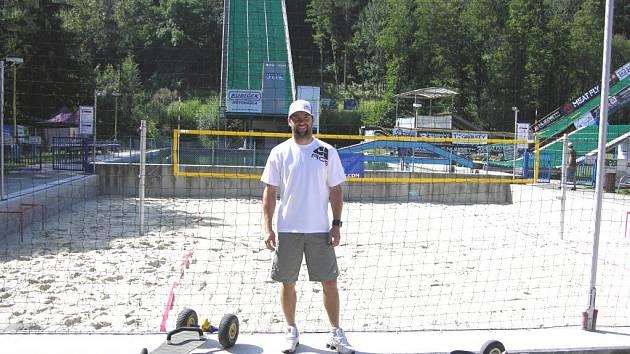 Aleš Valenta pózuje před můstky a beachvolejbalovým hřištěm v Acrobat Parku ve Štítech, který mu patří.