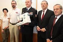 Ředitel věznice Mírov Vladimír Lang (uprostřed) a hejtman Olomouckého kraje Martin Tesařík (druhý zprava) při předání šicích strojů pro projekt Humanita