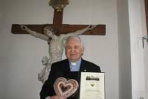 V klopě saka se otci Stanislavovi blýská zlaté srdíčko. V rukou drží dekret o udělení ceny Zlaté srdce Evropy, ke kterému navíc dostal i sladké perníkové srdce.