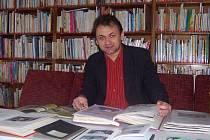 Ředitel Miloš Richter si prohlíží staré kroniky přibližující historii knihovny.