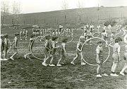 NA HŘIŠTI. Spartakiádní slavnost na hřišti vKamenné, rok 1980. Na fotografii je nejmladší žactvo vmodrých úborech cvičící sobručí.