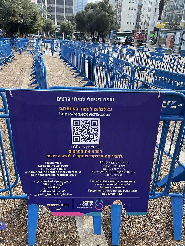Na náměstí v Tel Avivu je také velké testovací centrum na PCR testy COVID-19. Informační cedule u vstupu.