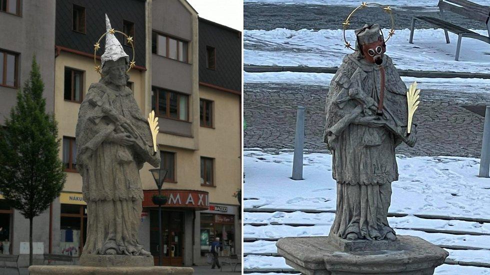 Socha svatého Jana Nepomuckého na náměstí v Jeseníku s čepičkou proti 5G záření (vlevo). Socha svatého Jana Nepomuckého na náměstí v Jeseníku s plynovou maskou (vpravo)