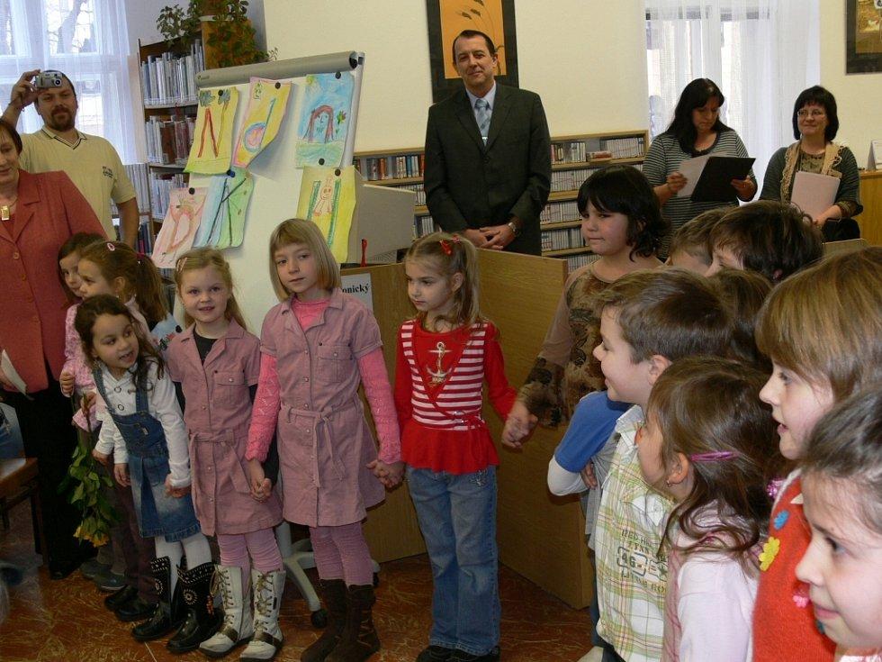 Starosta Šumperku Zdeněk Brož předává v knihovně dětem jejich první vysvědčení.