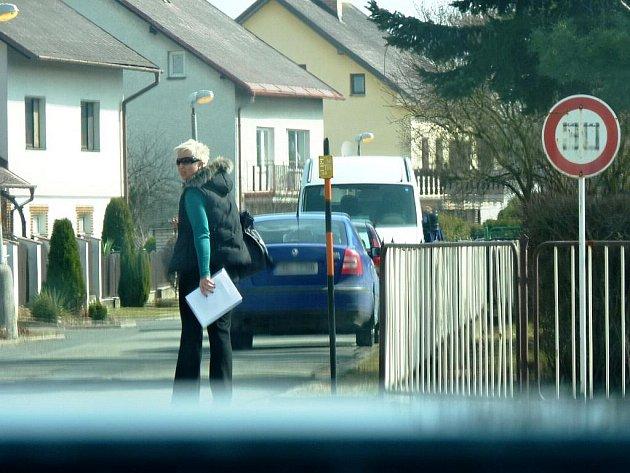 Učitelka se chystá vstoupit do modrého vozu, firemního auta štítecké radnice, ve kterém čeká starosta Štítů Jiří Vogel