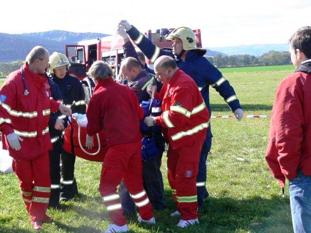 Záchranáři odnášejí popáleného rogalistu k vrtulníku.