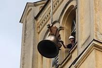 Zdvihání a instalace nového zvonu do věže kostela ve Vidnavě a snášení jeho starého předchůdce.