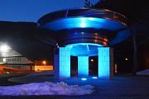 Oběžné kolo, které na Dlouhých stráních před lety dosloužilo a dnes před vstupem do podzemí vítá exkurze, v modrém odstínu.