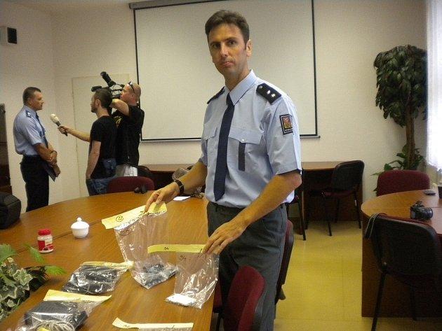 Policejní mluvčí Josef Bednařík ukazuje zadržené telefony, ze kterých stíhaný posílal výhrůžky.