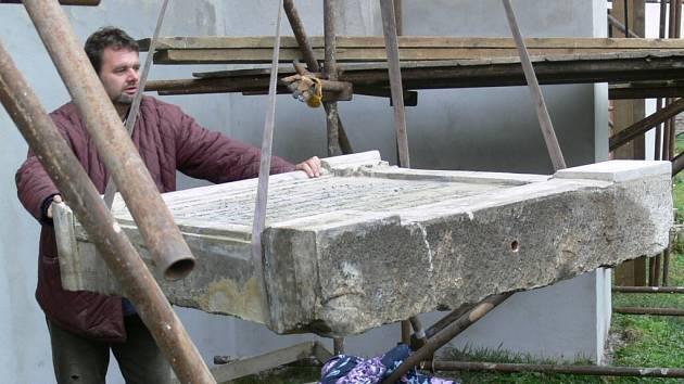 Restaurátor René Seifert osazuje pomníky k východní stěně kostela ve Velkých Losinách.