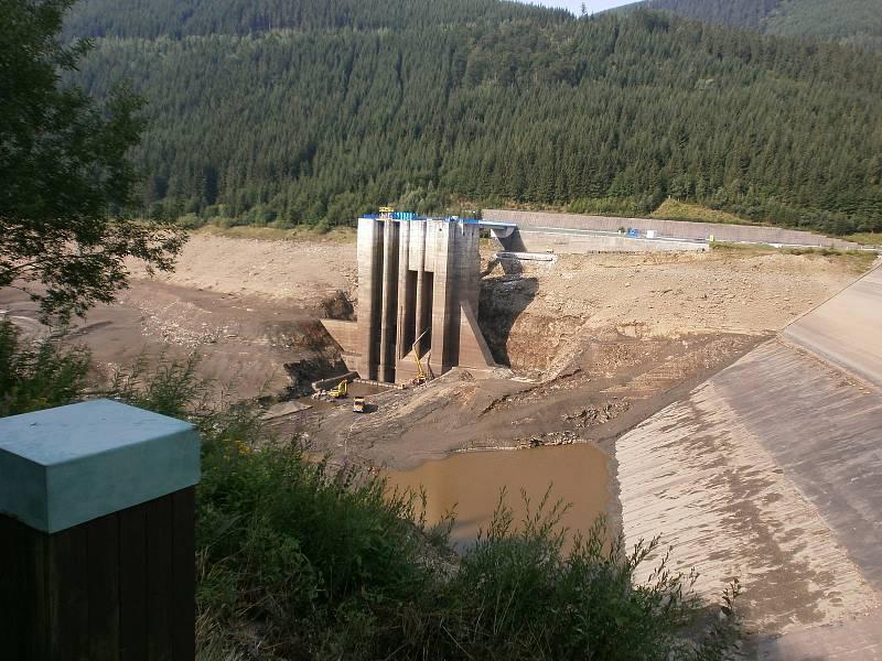 Vypuštěná nádrž Přečerpávací vodní elektrárny Dlouhé stráně před vyproštěním jeřábu. Ten se na snímcích nachází u paty sdruženého objektu.