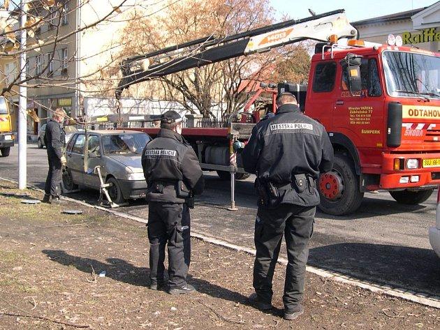 Odtahová služba se chystá naložit vůz, který brání úklidu šumperské ulice