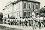 SPARTAKIÁDA. Cvičenci na snímku zroku 1970 se řadí ke slavnostnímu průvodu obcí ke kulturnímu domu, kde proběhne místní spartakiádní cvičení. Na fotografii jsou žáci základní školy sučitelem Karlem Štefkem sbudovou základní školy vpozadí.