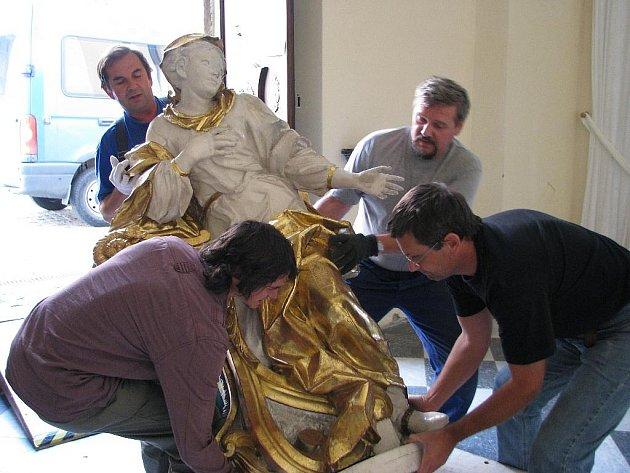 Řemeslníci vracejí sochu anděla na jeho místo v šumperském klášterním kostele