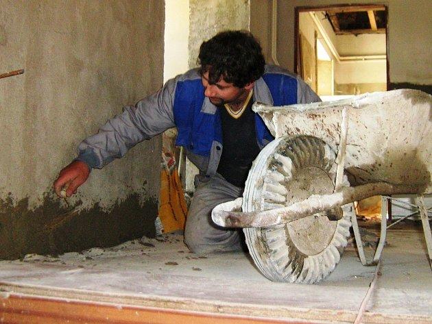 Řemeslník pracuje na opravě kulturního domu v Písečné