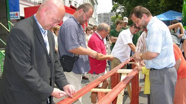 První mince vložili do speciální dřevěné drážky (zleva v popředí) Vladimír Velčovský, Marek Zapletal a Petr Suchomel.