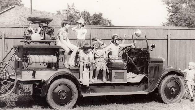 1. HASIČI. Radost malých dětí zhistorického hasičského auta vroce 1980 ve dvech oslav stého výročí založení postřelmovských hasičů. Tuto dobovou stříkačku má sbor ve svém vlastnictví dodnes.