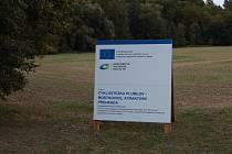 Na plánovanou výstavbu cyklostezky podél severního břehu plumlovské přehrady upozorňuje na louce u Plumlova informační tabule o projektu. Do země se ale zatím ještě nekoplo. Stav k 5. září 2019