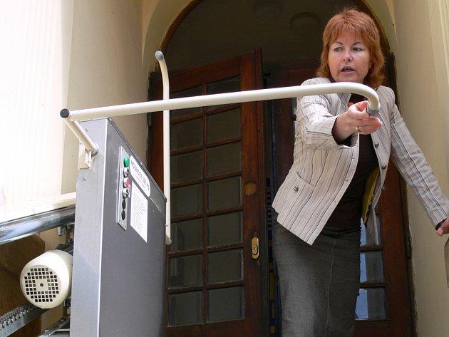 Ředitelka divadla Alena Spurná předvádí obsluhu plošiny pro vozíčkáře.