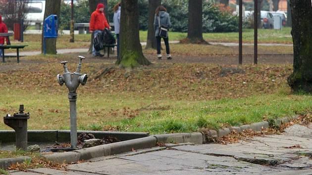 Voda z hydrantu zamrzá na rozbitém chodníku.