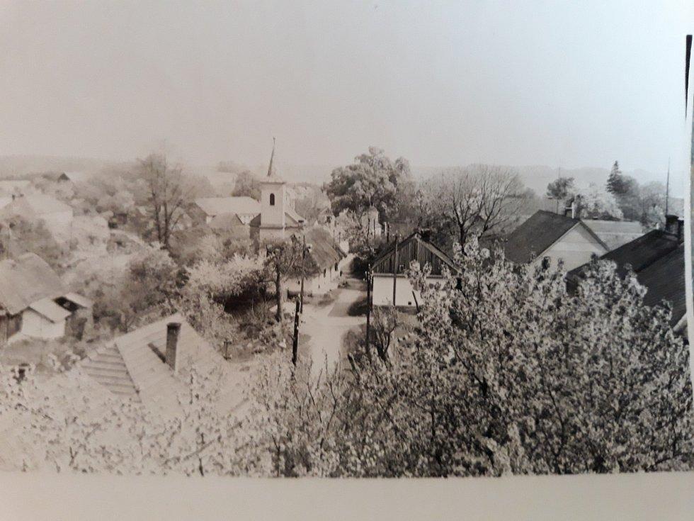 POHLED NA OBEC. Fotografie byla pořízena z okna školy. Na návsi je možné vidět kapli svaté Anny, která byla postavena v roce 1902. Dodnes slouží k pravidelným mším.