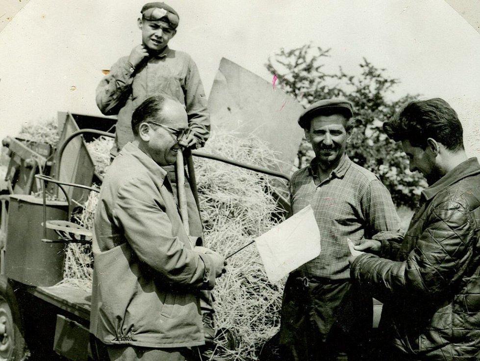 Tajemník MNV Vítězslav Dorazil předává vlaječku a peněžitou odměnu za dobrou práci při vázání slámy.