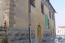 Zelenobílý poutač infocentra na zdi prostějovského zámku