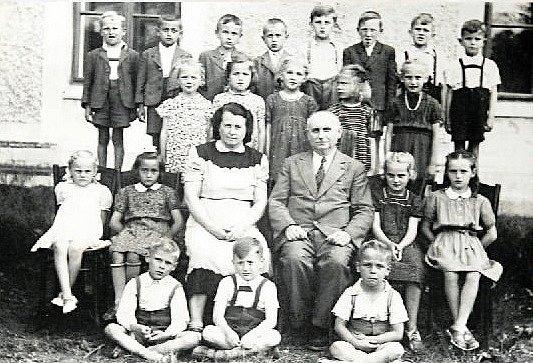 TŘÍDA 1. b ve školní roce 1950/1951. Do první třídy nastoupilo přes 40 dětí. Na fotografii jsou kostelečtí spolužáci s třídní učitelkou Marií Neokařovou a ředitelem školy Osladilem.