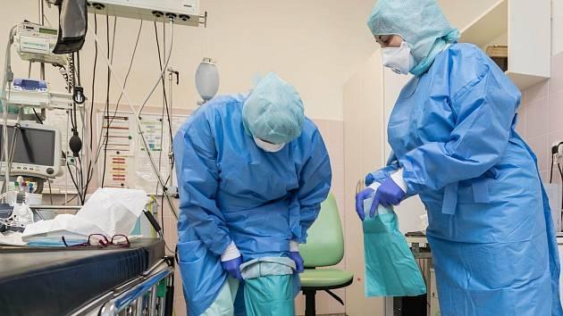 Zdravotníci se oblékají do ochranných obleků.