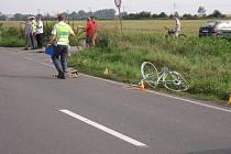 Policisté u místa nehody, na krajnici leží rozbité kolo.