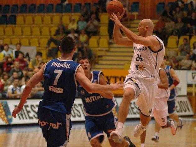 Polský pivot – silák ve službách prostějovských basketbalistů Robert Tomaszek (ve výskoku) razantně prochází obranou Nové huti Ostrava v jednoznačně vítězném duelu.